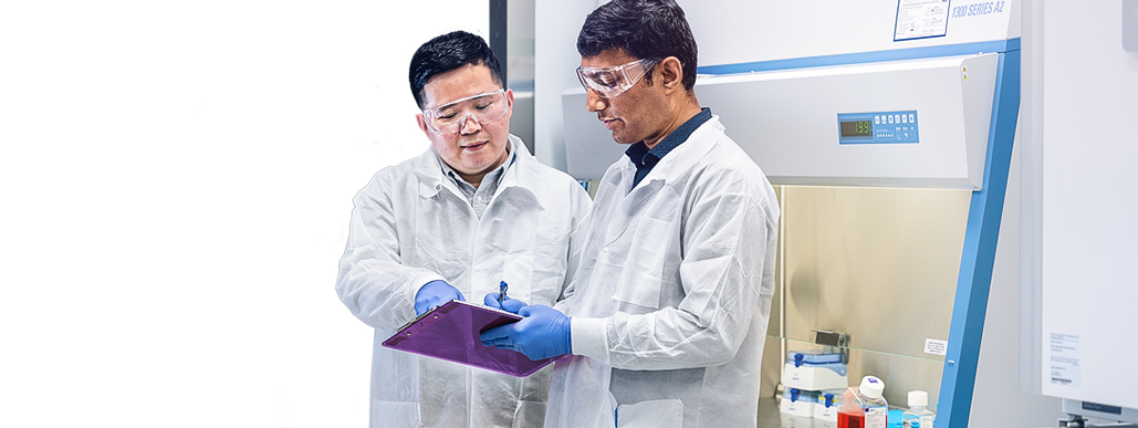 Two lab workers in protective wear